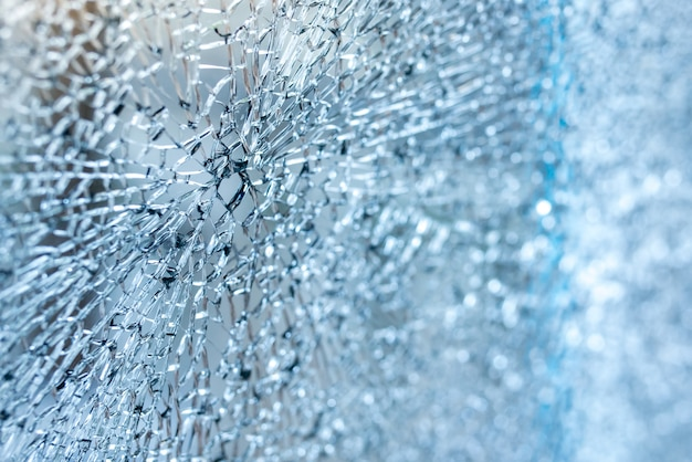 Крупный план сломанного лобового стекла автомобиля. синий оттенок