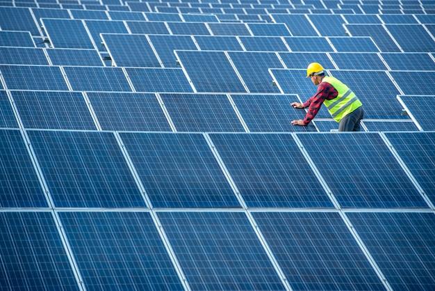 アジアの男性労働者が太陽電池パネルを設置しようとしています。太陽光発電所では、アジアの労働者が注文を受け、太陽電池を設置しています。