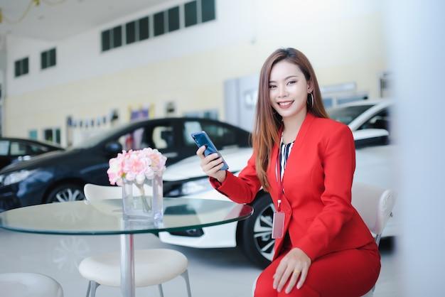 自動車のショールームで新車を販売するために顧客と電話で話している自動車販売員、美しい女性、アジアの女性