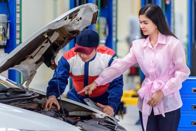 Автомеханик и красивые азиатские клиенты разговаривают и соглашаются починить машину девушки в автосервисе.