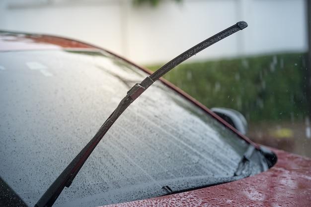 雨季に雨の中で駐車し、フロントガラスからフロントガラスを取り除くワイパーシステムを備えた車
