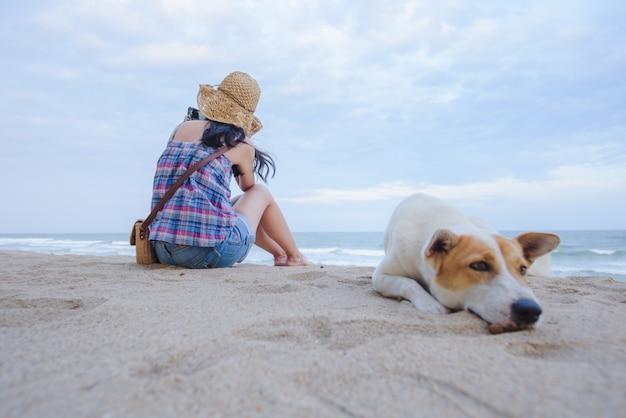 Молодые азиатские женщины печально сидят на пляже у моря с собакой, сидя на пляже на заднем плане