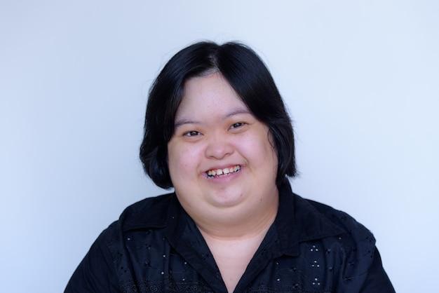 Крупный план азиатской девушки с инвалидностью. синдром дауна у детей. пухлая и милая улыбка на белом фоне