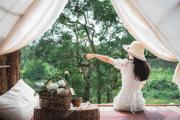 Красивый азиатский женский турист на ее комнате в одичалом