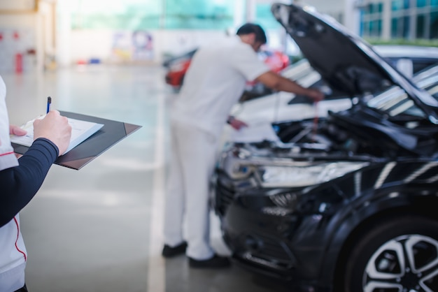 アジアの自動車整備士はエンジンをチェックし、車のエンジンの問題を分析してクリップボードに書き込みます。機械の修理、車の修理、メンテナンスのチェックリスト。