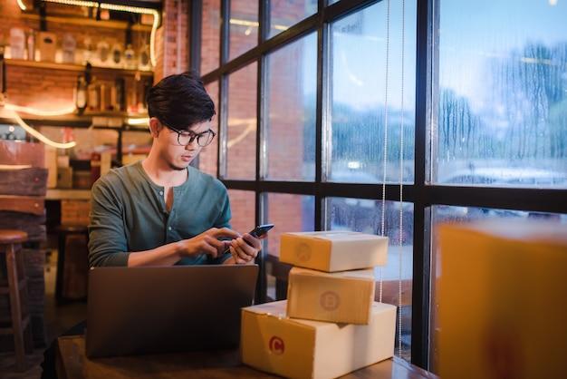 オンラインでアイデアコンセプトを販売する小包と木製の床にコンピューターと携帯電話で座っている若い男。