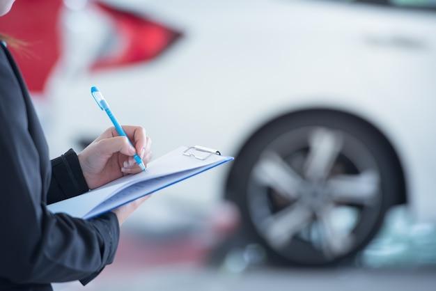 アジアの女性エンジニアと技術者はメカニックをチェックし、自動車修理店で車のリストを検査しています