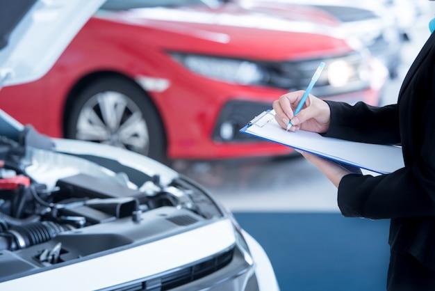 Азиатские женщины-инженеры и техники проверяют механика и осматривают автомобиль в автосервисе по списку на доске.