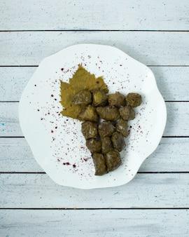 木製のテーブルに詰められた肉とブドウの葉のドルマ