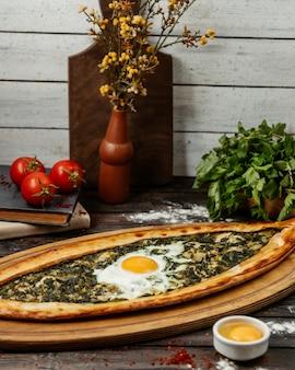 Турецкое блюдо пиде с зеленью и яйцом