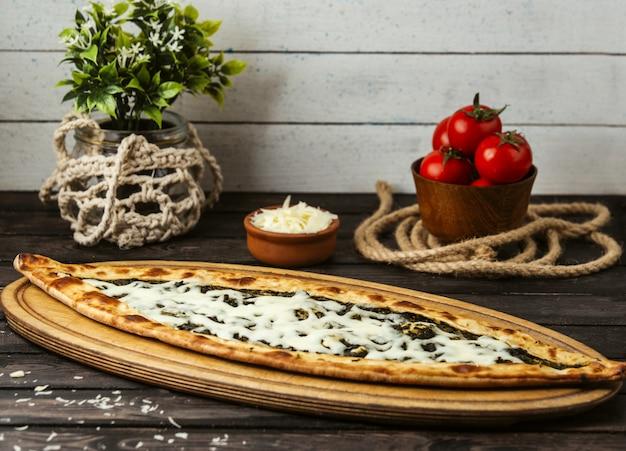Турецкий традиционный пиде с сыром и зеленью на деревянной доске