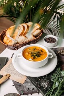 白いボウルにカリフラワーとジャガイモのスープの側面図
