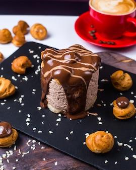 Вид сбоку шоколадного десерта, украшенного профитролями на черной деревянной доске