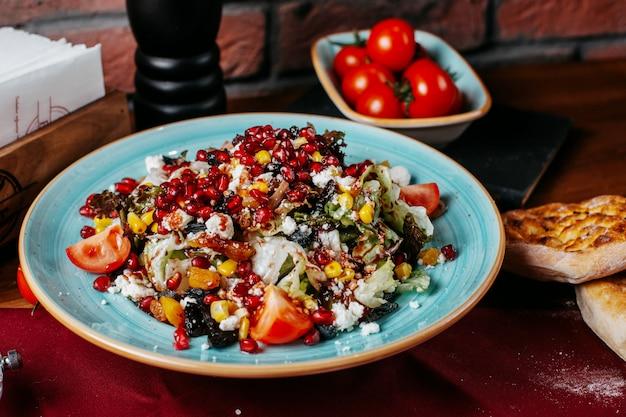 Вид сбоку свежего салата с капустными помидорами белого сыра и граната на тарелке