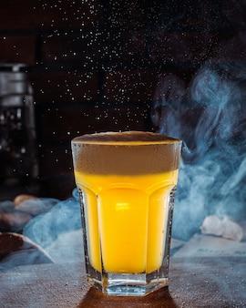 テーブルの上の軽いビールのグラスの側面図