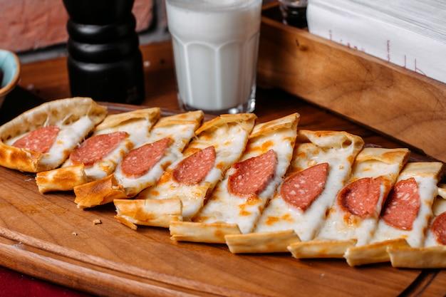 Вид сбоку турецкого пиде с колбасой салями, на деревянной разделочной доске