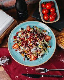 Вид сверху свежий салат с капустными помидорами белого сыра и граната на тарелке