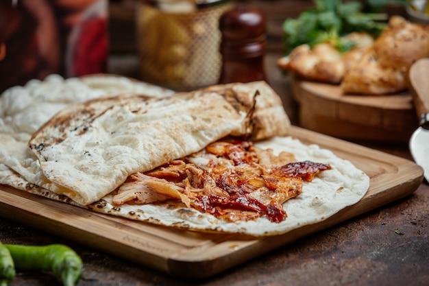 Донер из куриного шашлыка с кетчупом внутри лепешки на деревянной доске