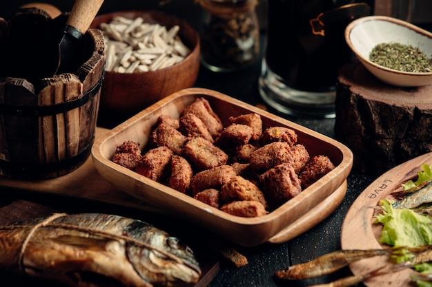 Куриные наггетсы как закуска к пиву на деревянной тарелке