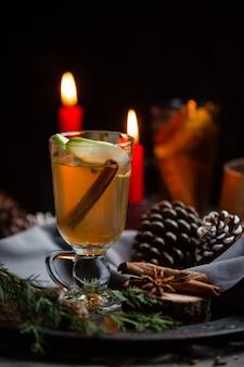 Зимний напиток с палочкой корицы и ломтиком яблока в рождественском столе
