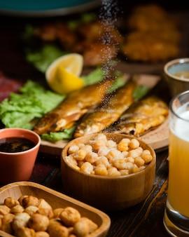 ビール、塩味のゆでエンドウ豆、干しスモーク魚のビールのセットアップ