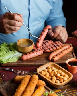 ひよこ豆のローストとコロッケのグリルソーセージを食べる男性