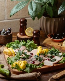 Ломтики колбасного ассорти в форме сердца на деревянной тарелке