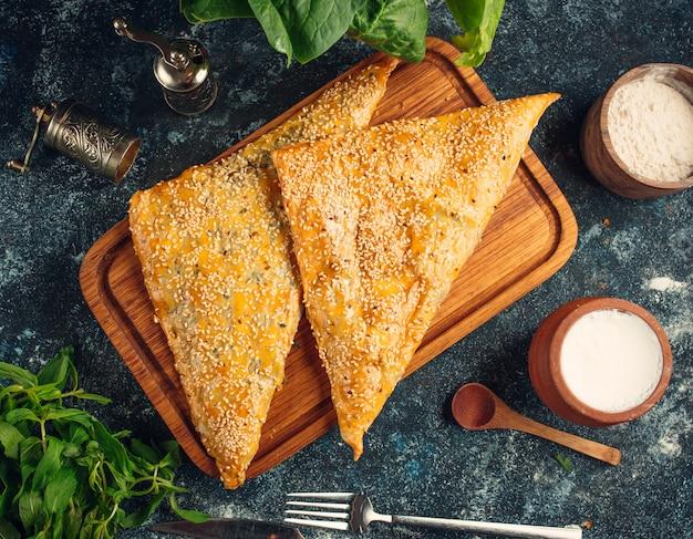 Запеченный пирог в форме треугольника с кунжутом
