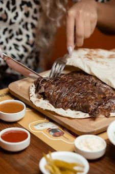 女性は、マヨネーズとケチャップを添えてフラットブレッドにラムステーキをカット