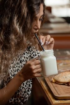 Женщина пьет айран йогуртовый напиток с соломой из банки в кафе