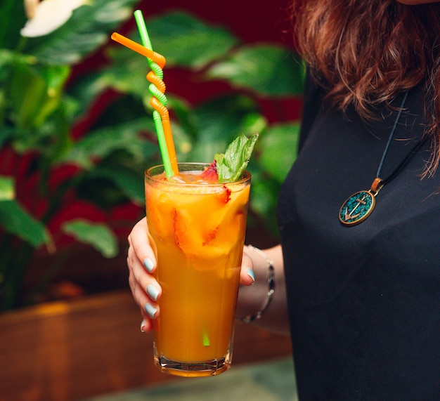 イチゴとオレンジのスライスとオレンジジュースを保持している女性