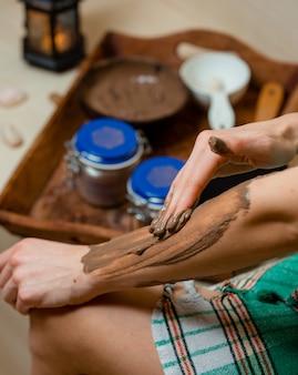 Женщина в хамаме наносит коричневую грязевую маску на руки