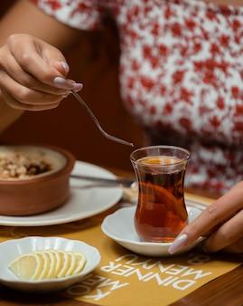 レモンと伝統的なアゼルバイジャングラスで紅茶を飲む女性