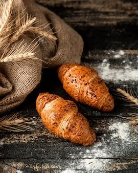 クロワッサンと小麦粉と小麦のテーブルを充填