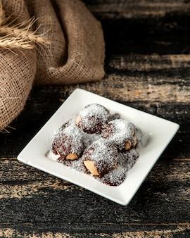 Профитроли с шоколадным сиропом и кокосовой стружкой на тарелке