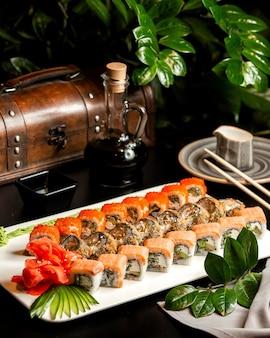 Суши-сет филадельфия калифорния и горячий ролл с имбирным огурцом и соевым соусом на тарелке