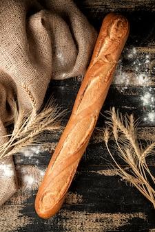 テーブルの上の小麦粉と小麦のバゲットのパン