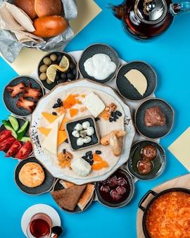 Набор для завтрака с сыром и сухофруктами на тарелке с черными зелеными оливками, сливочным инжиром и клубничным джемом