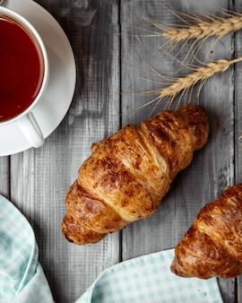 テーブルの上のお茶のカップとクロワッサン