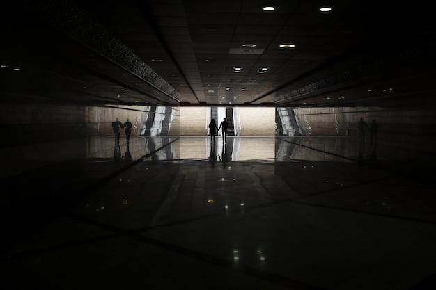 遠くを歩いている人と一緒に暗い地下鉄