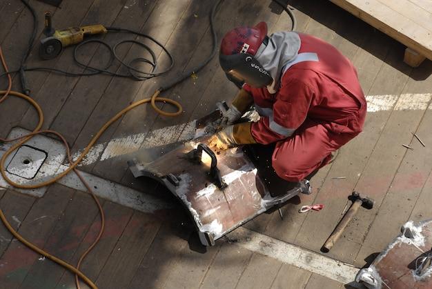 Рабочий в рабочем костюме фиксирует металлическую стойку