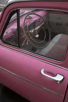 古い車に近いピンクの車