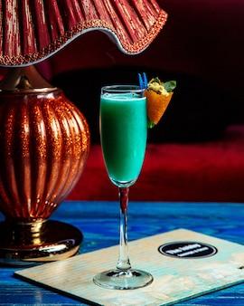 Алкогольный коктейль с апельсиновой коркой и цветами, вид сбоку
