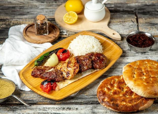 Мясо на гриле с рисом, перцем, помидорами, вид сбоку