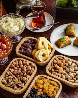 Вид спереди сладости чайный набор орехи фисташки сухофрукты пахлава со стаканом чая