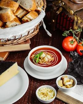Вид спереди томатный суп с крекерами и сыром помидоры и хлеб на столе