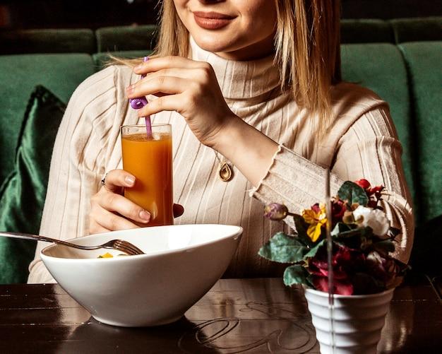 正面の女の子がテーブルの上のサラダのプレートとオレンジジュースを飲む