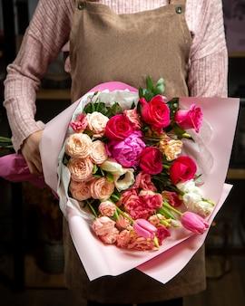 Вид спереди девушка держит красивый букет из разноцветных роз тюльпанов и пионов в бумажной обертке