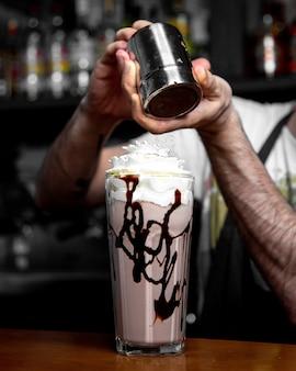 Человек льет корицу на ледяной кофе, вид сбоку