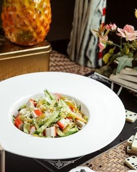 Вид сбоку крабовый салат без майонеза на тарелке